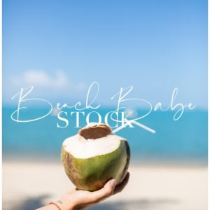 A hand holding a young coconut against bright blue sea backdrop.