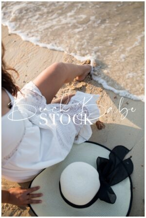 A woman in a white dress sitting on the beach in sand with waves at her feet.