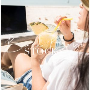 Woman drinking pineapple drink sitting on the beach