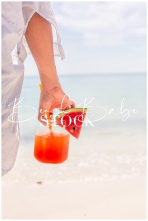 Hand Holding a Pink Cocktail on the Beach