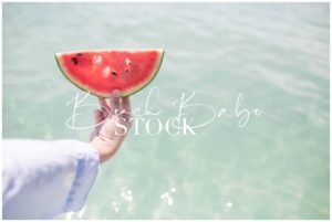 Hand Holding Watermelon against the sea