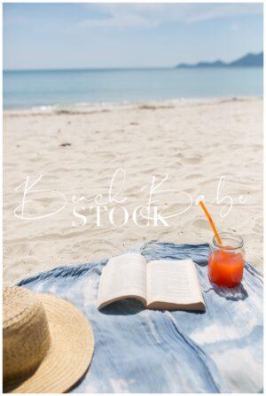 Beach towel, sunhat, book, and cocktail