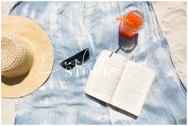 Flatlay of Beach towel, sunhat, book, and cocktail