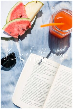 Flat-lay beach details, book, fruit and sunglasses